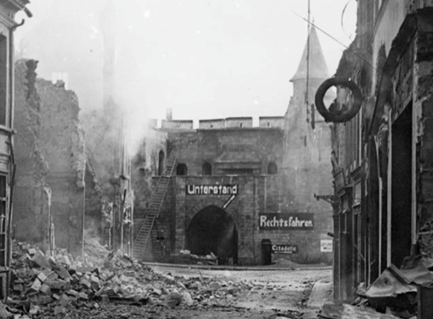 The smouldering ruins of a street in Cambrai, three days after the British entry, 10 October 1918. Note German notices indicating an air raid shelter and the direction to the citadel. IWM © Q11804