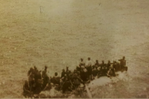 Survivors on a crowded upturned boat waiting to be taken off