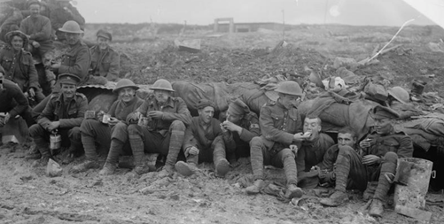 Canadian troops eating rations whilst seated on muddy ground outside a shelter near Pozieres during the final stages of the Battle of the Somme, October 1916